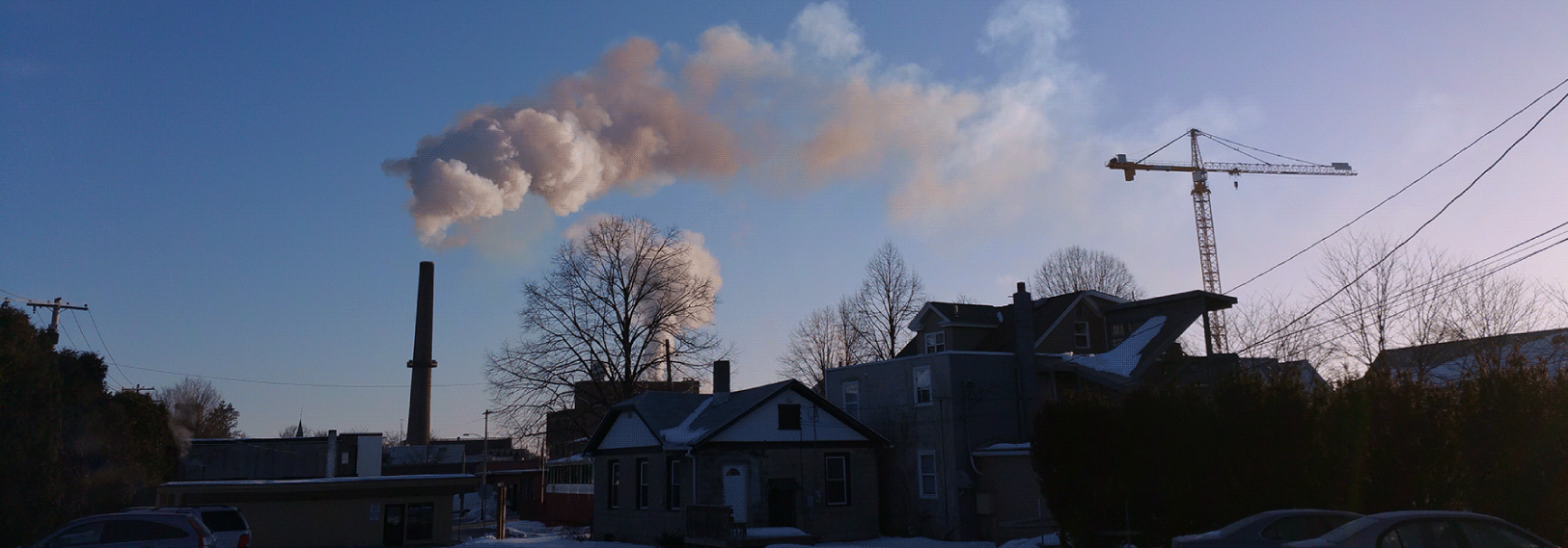 Smoke rises from a smokestack into a clear, blue morning sky